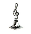 Treble clef d from bright metal on an original support Royalty Free Stock Photography