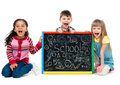 Tree cheildren look at little blackboard sitting on the floor isolated white background Royalty Free Stock Image