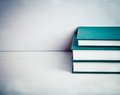 Tree green books pile composed of on a white reflective table Royalty Free Stock Photo