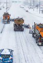 Tree lined up snowplows clearing the highway removing swno on a cold snowy winter day Royalty Free Stock Images
