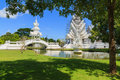 Tree shade on green grass in white temple thailand Stock Image