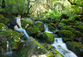 Trekker resting next to a river torrent Royalty Free Stock Image