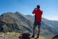 Trekker taking a photo with his smartphone on top of the mountain Stock Photography