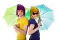 Trendy couple with sunglasses wigs and umbrellas over white background Stock Photography