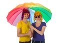 Trendy couple with sunglasses and wigs under an unbrella covered a rainbow umbrella Royalty Free Stock Images