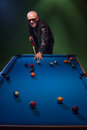 Trendy dude playing a game of pool in a nightclub Royalty Free Stock Photo