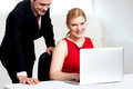 Trendy female boss working with man assisting Royalty Free Stock Images