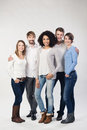 Trendy group of diverse young friends standing grouped around an attractive african american women on a grey studio Royalty Free Stock Image