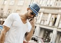 Trendy guy on the phone on street in city Royalty Free Stock Photo