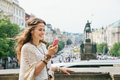 Trendy hippie woman with mobile on Wenceslas Square, Prague Royalty Free Stock Photo