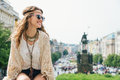 Trendy hippie woman tourist relaxing on stone parapet in prague smiling brunette wenceslas square the background saint Stock Photography