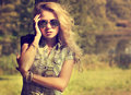 Trendy hipster girl on summer nature background in sunglasses touching her face modern youth lifestyle toned photo Royalty Free Stock Image