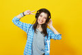 Trendy hipster young woman with headphones pretty girl showing peace sign and smiling on yellow background Stock Image