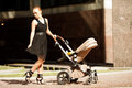 Trendy modern mother on a city street with a pram young mother fashionable walks child in the beautiful woman Royalty Free Stock Image