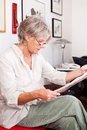 Trendy senior woman reading a newspaper modern wearing glasses sitting in her living room sideways portrait Royalty Free Stock Images