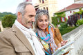 Trendy tourists using tablet during visit senior couple of on a trip Stock Photo