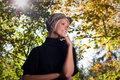 Trendy woman amongst autumn trees low angle upper body portrait of a smiling young in a cloth cap with sun flare Royalty Free Stock Photo
