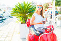 Trendy woman drinking takeaway coffee near her red moped on the Royalty Free Stock Photo