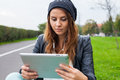 Trendy woman with tablet pc wearing headphones outdoors Royalty Free Stock Image