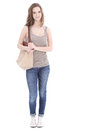 Trendy young female student wearing jeans and a pretty summer top and carrying a large cloth bag over her shoulder full length Stock Images