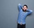 Trendy young man with beard relaxing portrait of a handsome hands behind head on gray background Stock Photography