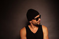Trendy young man portrait in a dark background looking away wearing beanie hat tank top and sunglasses Royalty Free Stock Photography