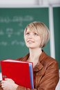 Trendy young student standing thinking female in a leather jacket in front of the blackboard with a large binder clutched in her Stock Image