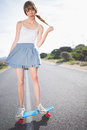 Trendy young woman balancing on her skateboard a deserted road Royalty Free Stock Image