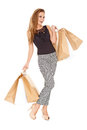 Trendy young woman with shopping bags posing in her high heels to show off her shapely figure and smiling at the camera Stock Photos