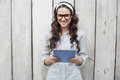 Trendy young woman with stylish glasses using tablet pc Royalty Free Stock Photo