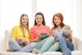 Tres adolescentes sonrientes con pc de la tableta en casa Fotos de archivo libres de regalías