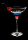 Tri color cocktail martini with a cherry on black background Royalty Free Stock Images