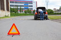 Triangle warning sign on road with driver in car Royalty Free Stock Photo