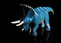 Triceratops dinosaur toy figure head against black background with reflection Royalty Free Stock Photo