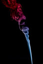 A trickle of blue and red smoke on black background Stock Photography