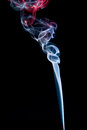 A trickle of blue and red smoke on black background Stock Images