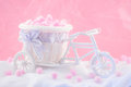 Tricycle souvenir on a pink background with fluffy donuts Stock Photography