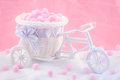 Tricycle souvenir on a pink background with fluffy donuts Stock Images