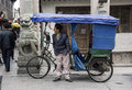 Tricycle taxi driver pudong shanghai a tired cyclist yawns loudly whilst waiting for his next customer Stock Image