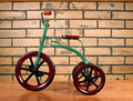 Tricycle vintage child s against a brick background Royalty Free Stock Photography