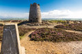Trig point with derelict windmill, Parys Mountain. Royalty Free Stock Photo