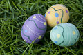 Trio of colorful Easter eggs laying in bright green grass. Royalty Free Stock Photo