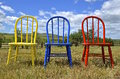 A trio of colorful Windsor wood chairs in an outdoor setting Royalty Free Stock Photo