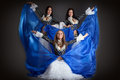 Trio of cute girls in traditional dance costumes posing studio Stock Images