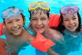Trio of happy children in swimming pool three friends with swim floats smiling on vacation Stock Photos