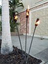 Trio of Tiki Torches near a Textured Wall Royalty Free Stock Photo