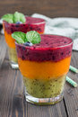 Triple smoothie in glass: kiwi-mint, mandarin-apricot and strawberry-blueberry Royalty Free Stock Photo