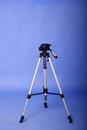 Tripod camera with blue background Royalty Free Stock Images