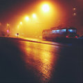 Trolley bus at night on city street in fog Royalty Free Stock Images