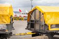 Trolleys loaded with luggage at an airport standing on the tarmac under yellow tarpaulins waiting to be on airplane Royalty Free Stock Photos